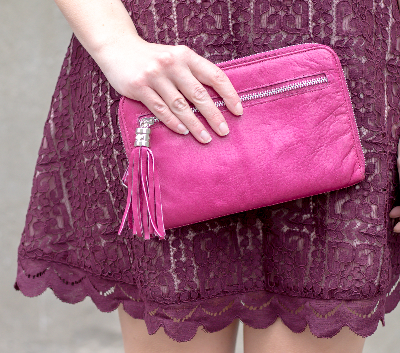 A fushia clutch styled with a lace dress