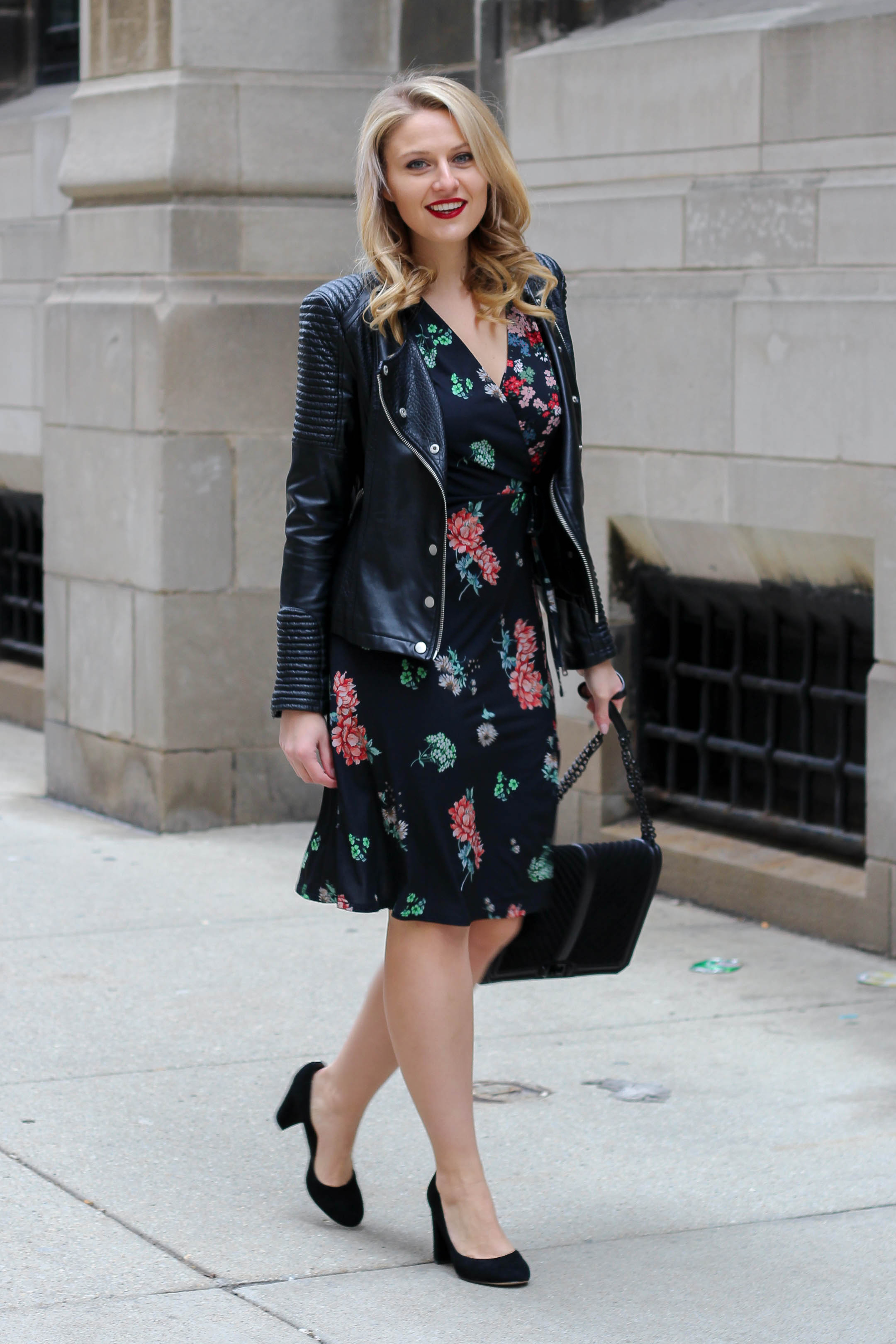 An easy date night outfit wearing a floral midi dress and faux leather biker jacket